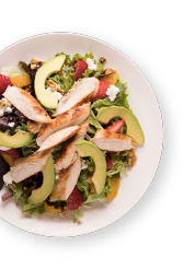 salad topped with chicken, avocado, and berries