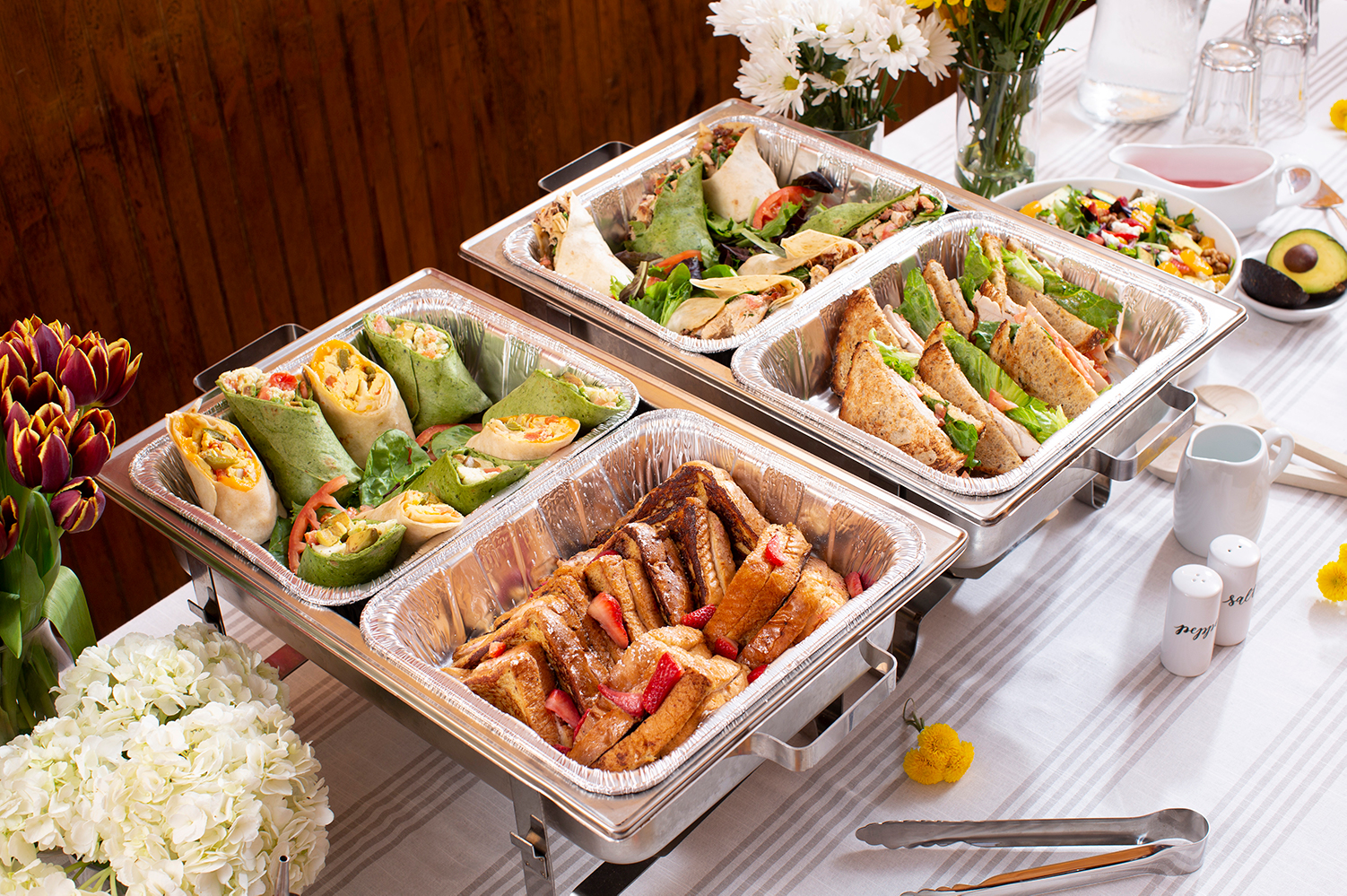 Catering spread with french toast, sandwiches, and wraps
