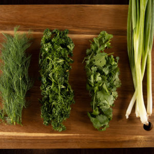 dill, parsley, cilantro, and green onion on a cutting board
