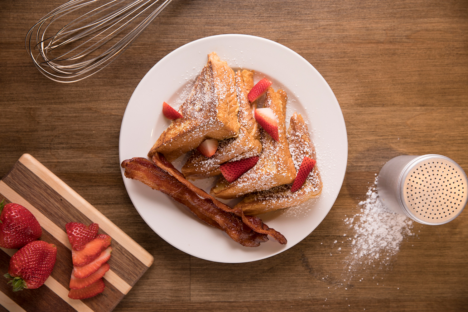 French toast stuffed with strawberries and topped with powdered sugar on a wooden table