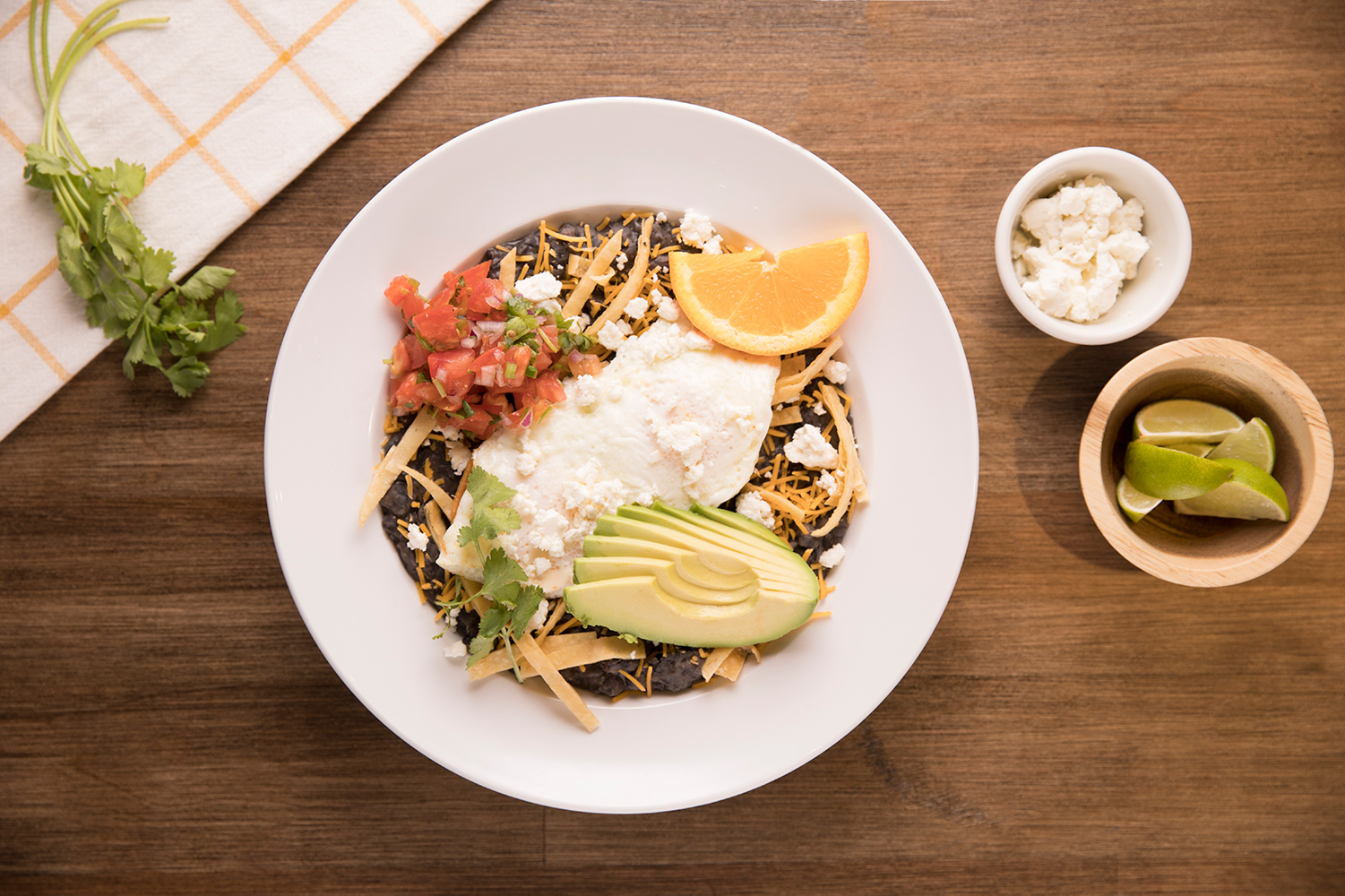 Huevos rancheros, black beans topped with eggs, cheese, salsa, and avocado