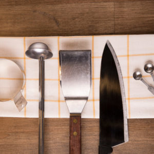 cooking tools including ladle, spatula, chefs knife, and measuring spoons